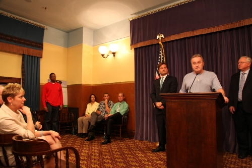 Kenneth Wyniemko introduces and acknowledges each of his fellow exonerees before addressing the media. From left: Exonerees Donya Davis (standing), Julie Baumer, and brothers Thomas and Raymond Highers, then Sen. Steve Bieda, Wyniemko and Sen. Rick Jones.