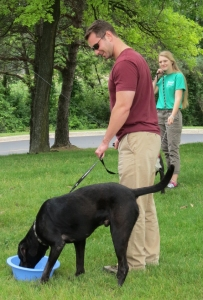 WMU-Cooley law student James Langley gives his shelter dog, Diesel, a drink before their walk on the trails.