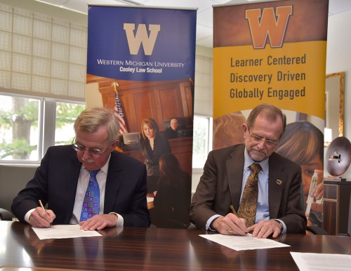 WMU-Cooley President Don LeDuc (left) and WMU President John M. Dunn signing a series of agreements to continue the expansion of legal education in west Michigan.